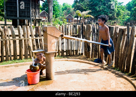 Children operating water pump, Kreung hilltribe village, near Banlung, Ratanakiri Province, Cambodia - Stock Photo