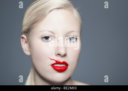 Portrait of a young blond woman with lipstick bleeding above her lip looking towards the viewer, imperfect, beauty - Stock Photo