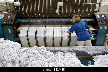 Janet Akgus working in the mangle hall at the handtowel rolls mangle machinery, Bardusch Uniform Rental & Laundry - Stock Photo
