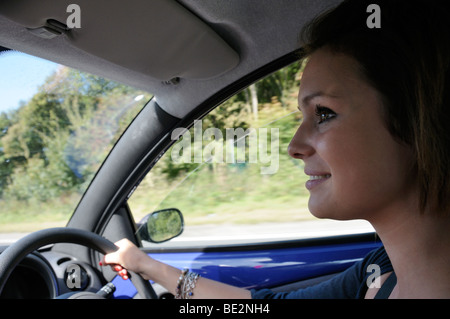 Stock photo of a teenage girl driving her own car after having just passed her driving test. The photo was taken - Stock Photo