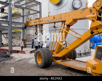 Mobile crane at an Indian construction site / factory building in an industrial area of India, in Surat, Gujarat. - Stock Photo