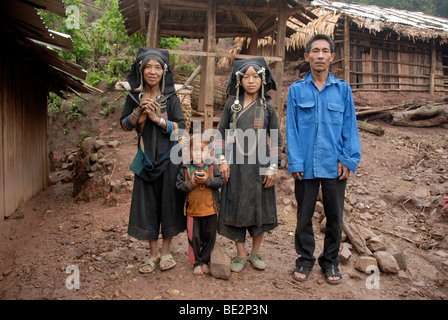 Poverty, portrait, ethnology, family of the Akha Pixor ethnic group in traditional dress, women, man, child, village - Stock Photo