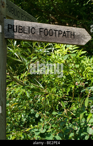 A wooden public footpath sign in the beautiful green english countryside - Stock Photo