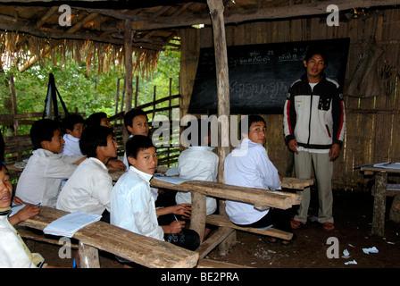 Poverty, education, school, simple village school, teachers with Akha Pixor students learning Laotian, village of - Stock Photo