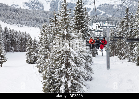 Skiers on a chairlift, Meribel ski resort in the Three Valleys, Les Trois Vallees, Savoie, French Alps, France - Stock Photo