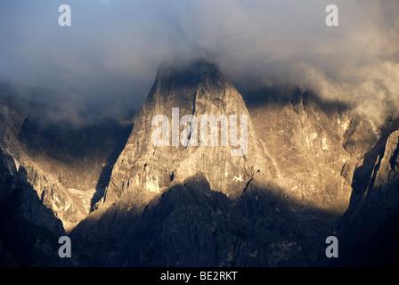 Mountain range in clouds, Alpenglow, evening sun on rocks, Jade Dragon Snow Mountain, Yulongxue Shan, Tiger Leaping - Stock Photo