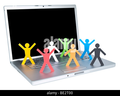 Several multicolored paper figures over a laptop keyboard. Isolated on white background. - Stock Photo