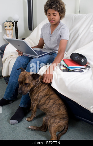 teenage boy working on his laptop computer at home and patting staffordshire bull terrier pet by his side - Stock Photo
