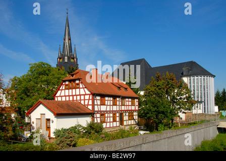 Half-timbered house in front of the Catholic parish church of St. Markus, Muehlheim am Main, Hesse, Germany, Europe - Stock Photo