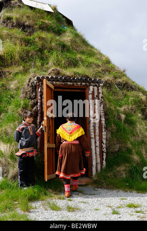 Woman wearing the traditional costume of the Sami People in front of her earth covered lodge, Hammerfest, Norway, - Stock Photo