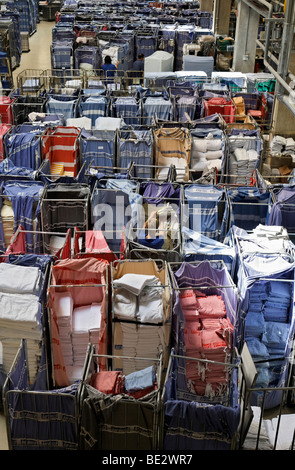 Freshly laundered rental linen sorted in trolleys and waiting in a room to be pressed - Stock Photo