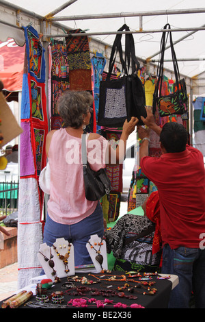 A woman shopping hand made bags on display at a street market in Panama City. - Stock Photo