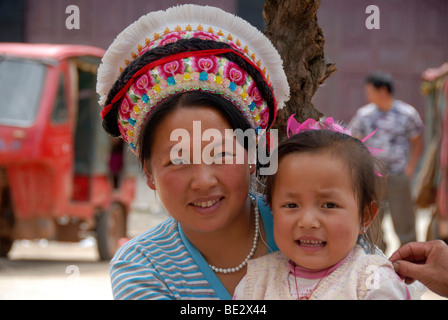 Portrait, ethnology, woman of the Bai ethnic group with typical head-dress and a toddler, Yongning, Lugu Hu Lake - Stock Photo