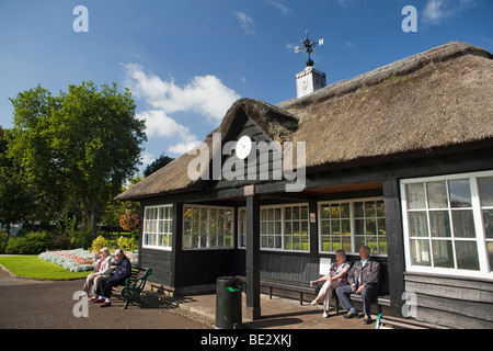 UK, England, Staffordshire, Stafford, Victoria Park, bowls pavilion retired people sat watching game in sunshine - Stock Photo
