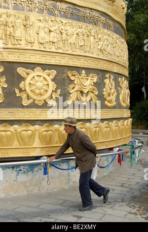 Tibetan Buddhism, Tibetan man, believer turning a giant prayer wheel, Zhongdian, Shangri-La, Yunnan Province, People's - Stock Photo