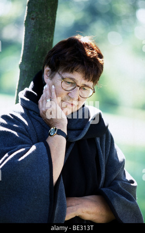 Woman alone looking down in park leaning against tree, mature woman alone sadness - Stock Photo