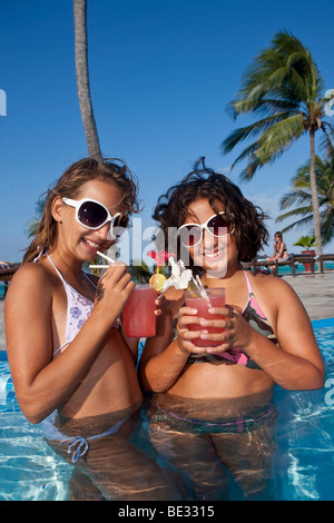 Two girls with sunglasses, about 12 years, drinking cocktails in a swimming pool - Stock Photo