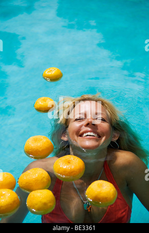 beautiful laughing young woman with long blond hair semi submerged in swimming pool with floating oranges - Stock Photo