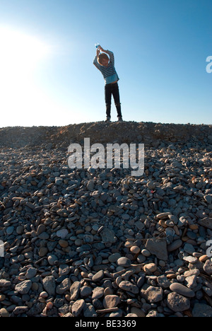 young boy standing on a shingle beach with a water bottle on his head in southern france - Stock Photo