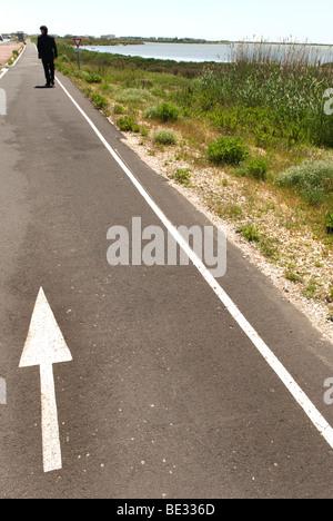 man dressed in dark suit walks away down coastal path with white arrow on it - Stock Photo