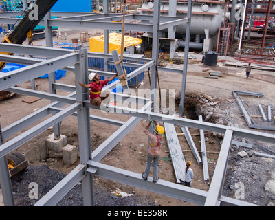 Indian construction workers assembling a factory building in an industrial area of India, in Surat, Gujarat. India. - Stock Photo