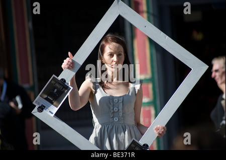 Street performer advertising her show with a frame in her hands for the 2009 Edinburgh Fringe festival, Scotland. - Stock Photo