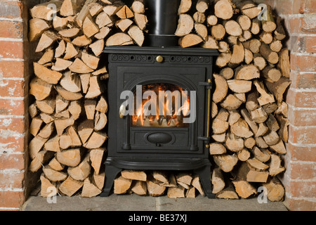 Wood burning stove surrounded by chopped and stacked firewood ready for burning - Stock Photo