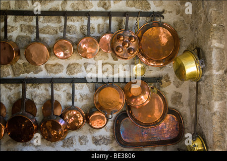 A range of brass pans hang in a French kitchen - Stock Photo