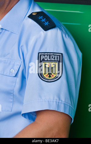 German policeman, epaulette of a police seargent, below it emblem of the Federal police, on the sleeve of a blue - Stock Photo