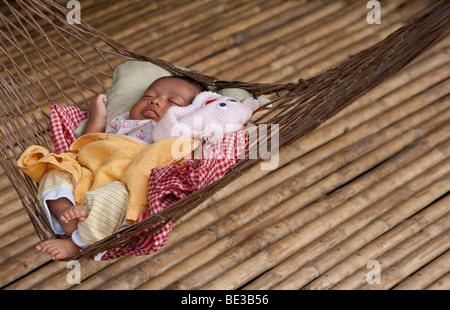 Young Cambodian baby sleeping in hammock, Kampong Chhnang, Cambodia - Stock Photo