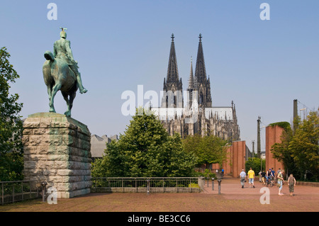 Equestrian statue of the Emperor Wilhelm II of Prussia, at the Hohenzollernbruecke Bridge, cathedral in the back, - Stock Photo