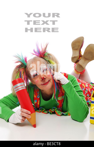 Clown with color pencil lying down and against white - Stock Photo