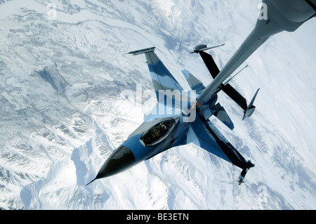 An F-16 Aggressor sits in contact position while a KC-10 Extender off-loads fuel. - Stock Photo