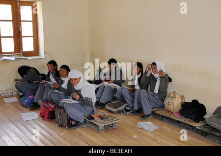 Students in uniform, on low benches in a class room, Phiyang, Ladakh, India, Himalayas, Asia - Stock Photo