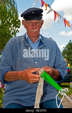 A fisherman mending fishing nets - Stock Photo