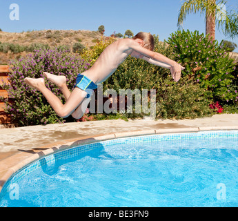 A boy, 7 years old, practicing racing dives in a pool - Stock Photo