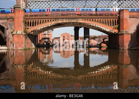 Train crossing Victorian railway viaduct bridge over Bridgewater Canal in Castlefield Urban Heritage Park conservation - Stock Photo