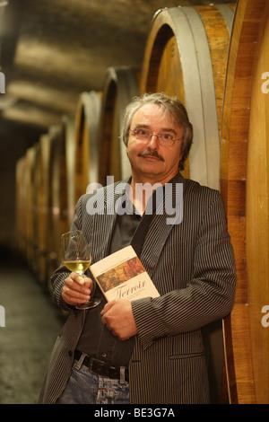 Viniculturist Reinhard Heymann-Loewenstein, owner of the Heymann-Loewenstein winery, in his wine cellar, holding - Stock Photo