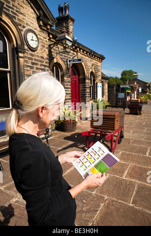 UK, England, Yorkshire, Keighley and Worth Valley Railway, woman waiting on Oakworth Station platform looking at - Stock Photo