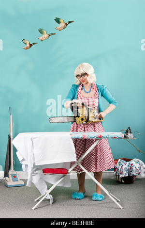 Retro Housewife taking a chainsaw to her ironing board - Stock Photo