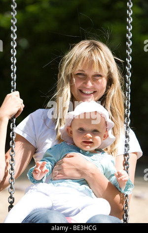 A young mother with her one-year-old daughter on a swing - Stock Photo
