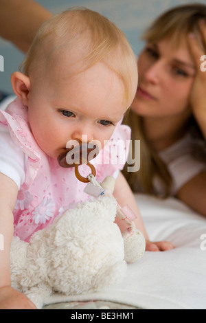 A young mother watching her one-year-old daughter - Stock Photo