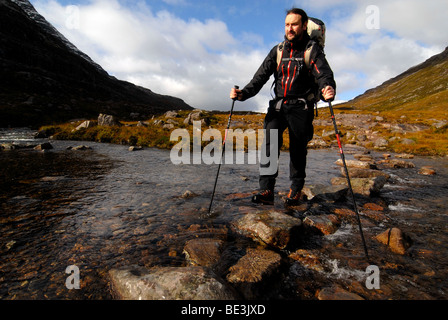 Hiker with trekking poles and backpack crossing a river in the Scottish mountains, Scottish Highlands, Stuca `Choir - Stock Photo