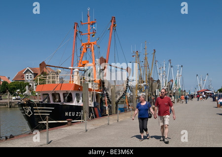 Tourists next to the fleet of shrimp boats in the harbor Neuharlingersiel, North Sea, East Frisia, Lower Saxony, - Stock Photo