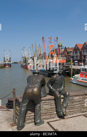 Bronze sculpture by of Old Fisherman and Young Fishermen in the port Neuharlingersiel, in the back shrimp boats, - Stock Photo