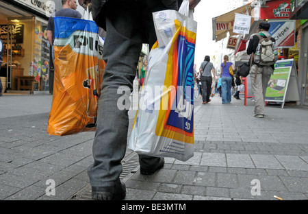 Old man after shopping at the discounters Aldi Sued and Plus, pedestrian area in Cologne, North Rhine-Westphalia, - Stock Photo