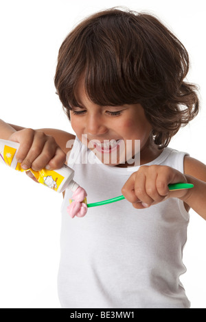Little boy is putting a lot of toothpaste on his toothbrush - Stock Photo