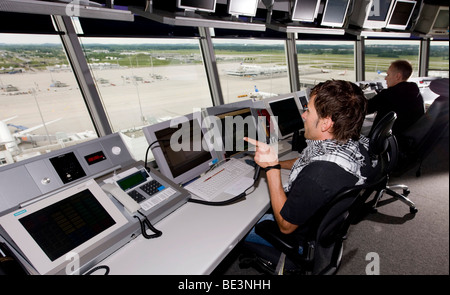 Two air-traffic controllers in 78 m high main tower of Munich Airport looking on to the apron West and Terminal - Stock Photo
