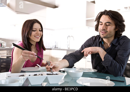 Young couple sitting at a laid table, having fun, eating with chopsticks - Stock Photo