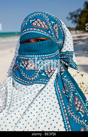 Veiled Muslim woman on the beach in Zanzibar, Tanzania, Africa - Stock Photo